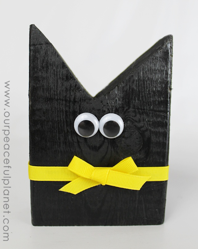 Make this simple black cat Halloween craft from 2x4 pieces, a little paint, ribbon and wiggle eyes! An inexpensive way to decorate your house for Halloween!