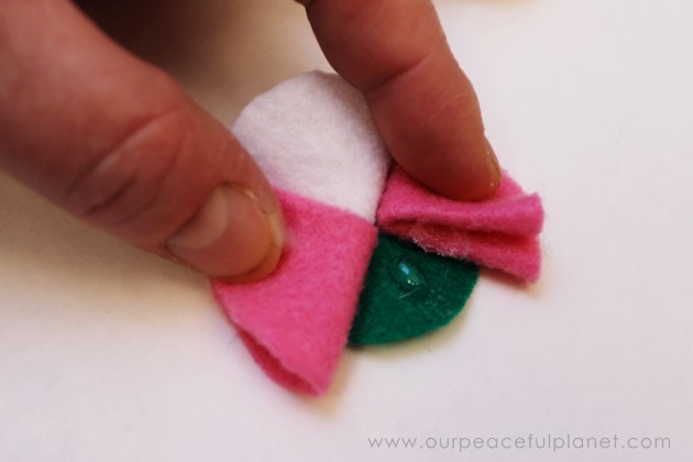 Learn how to make felt flowers in 5 minutes with scissors & hot glue. Use them to adorn many things from wreaths & other decor items to pins & hair clips!
