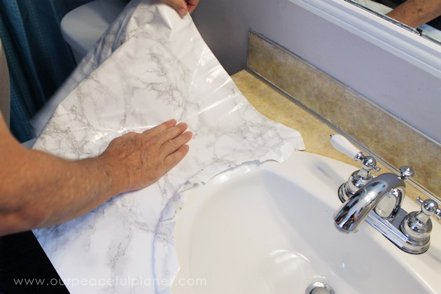 Transform your bathroom for only a few dollars with a contact paper countertop. You'll be amazed at how beautiful it looks & so will your family & guests!