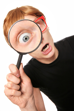 Excited nerd with magnifying glass