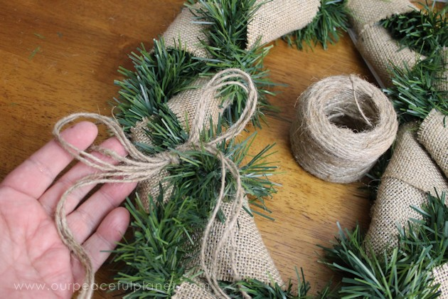 Promote the meaning of the season with this Christmas Peace Wreath using some inexpensive garland, burlap, a foam board and hot glue. It's simple and quick!
