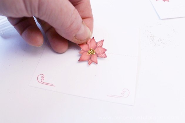 Download beautiful free printable poinsettia Christmas placecards. All you need are scissors and some glue and dab of glitter to add sparkle to your table!