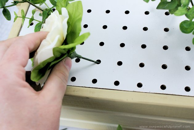 This DIY table centerpiece allows you to change decor year round for any occasion. Then lift out the pegboard insert to find candles for ambient lighting!